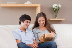 Couple on the couch with parcel Stock Images