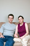 Couple on the Couch Smiling - Vertical Royalty Free Stock Photo