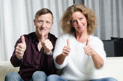 Couple on couch with thumbs up Stock Image