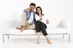 Couple on the couch watching TV. Couple  smiling on the couch watching TV Stock Photography