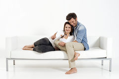 Couple on the couch watching TV. Couple embracing on the couch watching TV Royalty Free Stock Photos