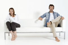 Couple on the couch watching TV. Separated couple on the couch watching TV Stock Photography