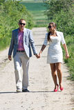 Couple on country road. Young couple walking dirt country road on sunny day Stock Photo