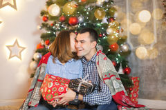 Couple couple in love under a blanket near the Christmas tree give each other gifts Royalty Free Stock Photos