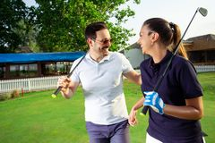 Couple at the course playing golf and looking happy - Image. Couple at the course playing golf and looking happy stock photos