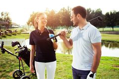 Couple at the course playing golf and looking happy - Image royalty free stock photography