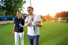 Couple at the course playing golf and looking happy. Young Couple at the course playing golf and looking happy royalty free stock photo