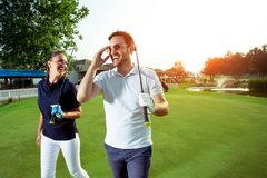 Couple at the course playing golf and looking happy. Young Couple at the course playing golf and looking happy stock images