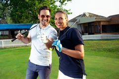 Couple at the course playing golf and looking happy. Young Couple at the course playing golf and looking happy stock photos