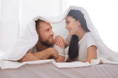 Couple covered in blanket looking into eyes. Cannot imagine my life without you. Radiant couple smiling while lying on a bed underneath a blanket and maintaining Royalty Free Stock Photography