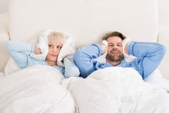 Couple Covering Ears While Sleeping On Bed Royalty Free Stock Images