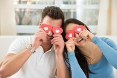 Couple covering eyes with the red hearts Royalty Free Stock Photography