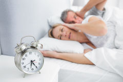 Couple covering their ears from alarm clock noise Stock Photos