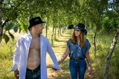 Cowboy and cowgirl couple with hats hold hands as they walk through avenue of trees on ranch royalty free stock image