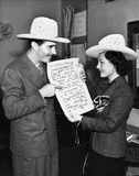 Couple with cowboy hats looking at sheet music Stock Photos