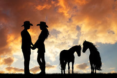 Couple of cowboys with horse at sunset Royalty Free Stock Photography