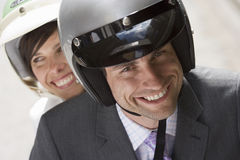 Couple in crash helmets riding on scooter in street, smiling, front view, close-up, portrait Stock Images