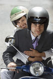 Couple in crash helmets riding on scooter in street, smiling, front view, portrait Stock Photography