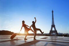 Couple of crazy tourists on holidays in Paris. Men and women having fun near Eiffel Tower, travel with luggage, tourism stock photography