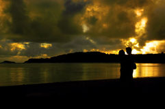 Couple Creation. Young couple greet the dawn in each others arms.  Golden sunrise is reflected in the ocean bay.  Cloud cover is also golden Royalty Free Stock Photos