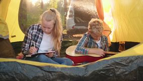 Couple creative teenagers stay in summer camp tent. Caucasian children draw picture paper sketch. Little blond boy play guitar inside shelter nature wood stock video footage