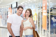 A couple with a credit card. Young attractive couple with a credit card in shop royalty free stock photography