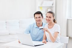 A couple with a credit card. Young couple with laptop and credit card at home stock photography