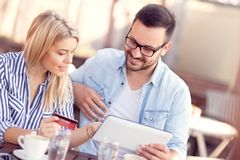 Couple with credit card in cafe looking at digital tablet together. Couple with credit card and digital tablet on online shopping tour from coffee shop stock photos