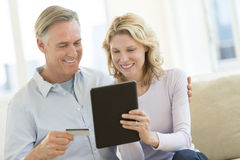 Couple With Credit Card And Digital Tablet Shopping Online. Happy mature couple with credit card and digital tablet shopping online at home Royalty Free Stock Photos