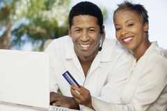 Couple With Credit Card And Headset Doing Online Shopping. Portrait of happy couple with credit card and headset doing online shopping Royalty Free Stock Photo