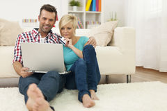 Couple with credit card and laptop. Couple sitting on carpet at home and doing shopping online royalty free stock image