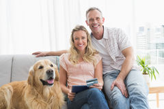 Couple with credit card shopping online. At home in the living room Royalty Free Stock Photo