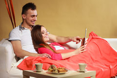 Couple with credit card shopping online by tablet. Couple with credit card shopping online Woman and men laying on sofa at home using new technology to buy stock image