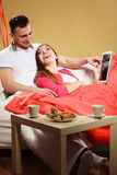 Couple with credit card shopping online by tablet. Couple with credit card shopping online Woman and men laying on sofa at home using new technology to buy stock photography
