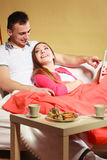 Couple with credit card shopping online by tablet. Couple with credit card shopping online Woman and men laying on sofa at home using new technology to buy Royalty Free Stock Images