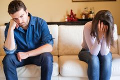 Relationship end and crying girlfriend on the sofa. Couple crisis after relationship breakup and boyfriend betrayal and infidelity confession royalty free stock photography