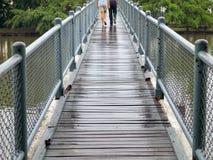 Couple cross-bridge. Two people walk across the bridge in the rain drizzle Royalty Free Stock Images