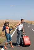 Couple crossing a long road Royalty Free Stock Images