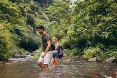 Couple crossing mountain stream. Couple holding hands as the men helps his girlfriend across the stream of their hiking trail. Man and women in forest, nature Stock Photos
