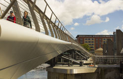 A couple crossing the new footbridge across the new flood barrier on the River Lagan at the Donegall Quay in Belfast Royalty Free Stock Photos