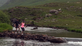 Couple crossing rocks in the middle of a flowing river Royalty Free Stock Image