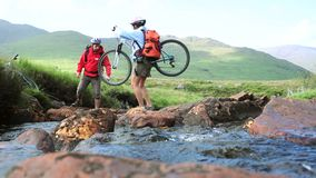 Couple crossing a stream together with their bikes Stock Photography