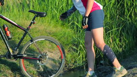 Couple crossing a stream together with their bikes in countryside stock video