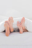 Couple crossing their feet under the duvet Stock Photo