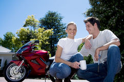Couple crouching beside red motorbike on driveway, woman holding mug of coffee, smiling, portrait (surface level) Stock Photography