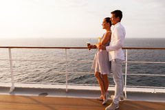 Couple cruise ship. Side view of smiling couple having cocktails on cruise ship at sunset royalty free stock photo