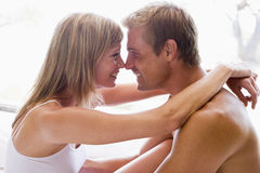 Couple cuddling. Man and women cuddling indoors smiling at each other stock photos