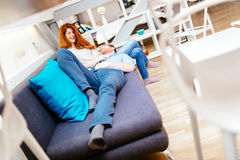 Couple cuddling in beautiful interior living room. While lying on sofa royalty free stock image