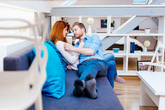 Couple cuddling in beautiful interior living room. While lying on sofa stock photo
