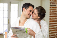 Couple cuddling while having tea and reading newspaper. In kitchen royalty free stock photo